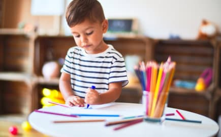 kid drawing using color pencil